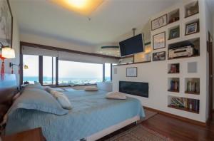 חדר השינה צופה לים, עם מחיצת נישות גבס למערכת שמע ונוי וטלויזיה תלויה