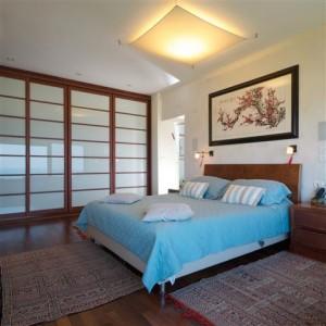 """חדר שינה עם ארון קיר גדול ודלתות הזזה שדות מזכוכית חלבית. בתקרה גוף תאורה """"שטיח"""" מבד."""